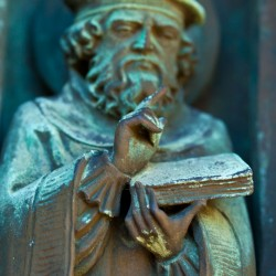 Man with book, detail from bronze doors, south porch