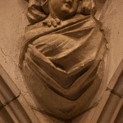 Stone carving of an infant in the Baptistry. One of the four stages of life.